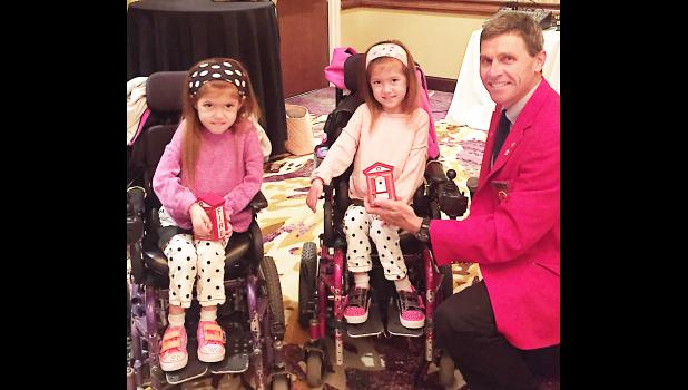 Iowa Firefighters Association President Mark McNees is shown presenting IFA banks to Aimee and Ashley martin, who were both promoting MDA awareness at the IFA Mid Year meeting.
