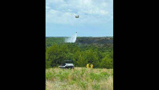 A Nebraska Army National Guard CH-47 Chinook helicopter drops water on a hot spot near the Niobrara River. Dry lightning sparked about 20 wildfires along Highway 11 north of Atkinson. Photo by Seth Peterson of the Nebraska Forest Service.