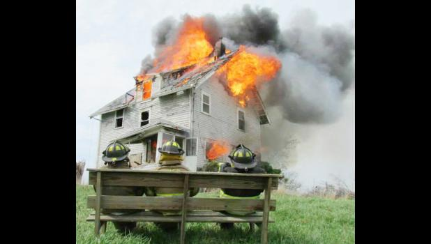 Three Maxwell firefighters watch the house burn after fire training was completed inside. The house, located in Polk County, was burned as part of a training exercise on May 4. Firefighters from Collins, Elkhart and Maxwell participated.