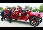 Hays firefighters help steer and push a 1921 REO Speedwagon that served as the first motorized fire truck for the Hays Fire Department back into the fire station after a presentation. Photo by Jolie Green of the Hays Daily News.